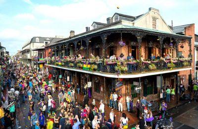 H ατμόσφαιρα της Mardi Gras: χρώματα, λάβαρα, καρναβαλιστές κάθε ηλικίας, παρελάσεις, χάντρες και μια μπάλα του φούτμπολ στον ουρανό του French Quarter