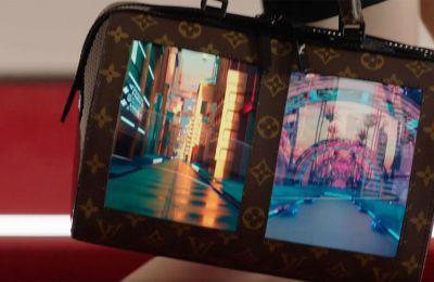 Ανοίγματα στον καμβά του Malletier (με το σήμα κατατεθέν LV, σε καφέ και κρεμ χρώμα) αφήνουν χώρο για τις OLED οθόνες.
