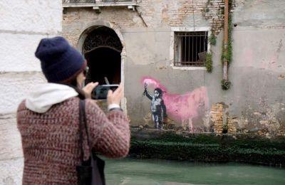 Μπροστά από τον πάγκο του, σε μιαν άκρη, ο καλλιτέχνης έχει βάλει μια μικρή πινακίδα στην οποία αναγράφεται «Venice in Oil»