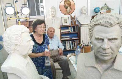 Ο Γιώργος Μαυρογένης και η σύζυγός του Ντίνα πλάι στα προπλάσματα της προτομής του Μίκη Θεοδωράκη, που φιλοτέχνησε για λογαριασμό του Ιδρύματος Φωτιάδη.