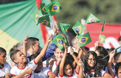 Mαθητές με σημαίες της Βραζιλίας κατά την τελετή αφής της ολυμπιακής φλόγας, το 2016.