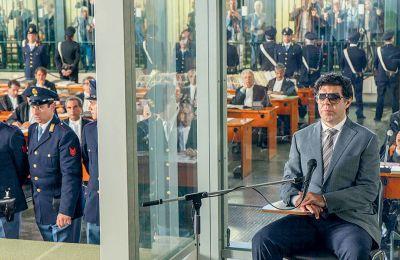 Στην αίθουσα του δικαστηρίου, παρακολουθούμε δεκάδες μαφιόζους σε ειδικά κελιά να αποδοκιμάζουν και να απειλούν τον άνθρωπο που τους έφερε εκεί